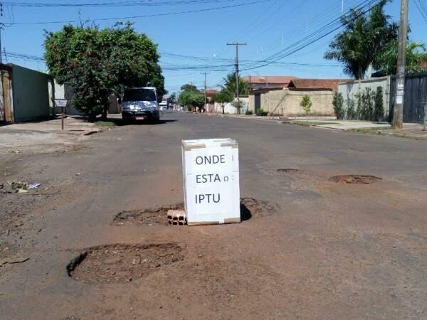 """Placa com a mensagem """"Onde está o IPTU"""" sinalizando um buraco na Av Aeroporto, bairro Sto Amaro em Campo Grande (Foto: Direto das ruas)"""