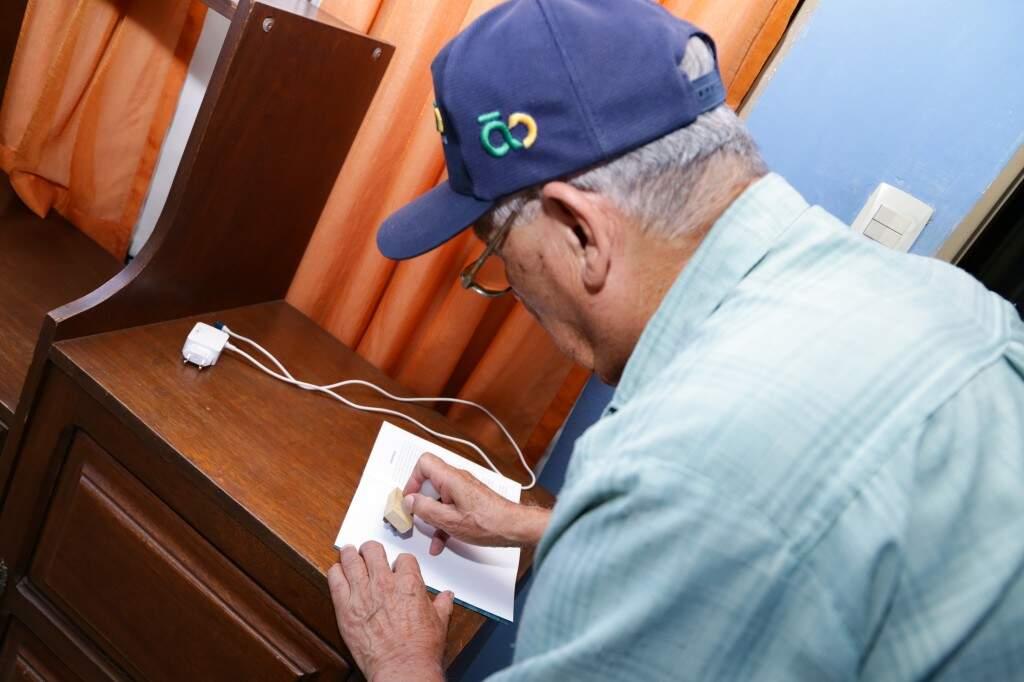 Luis autografando livro com carimbo. (Foto: Kísie Ainoã)