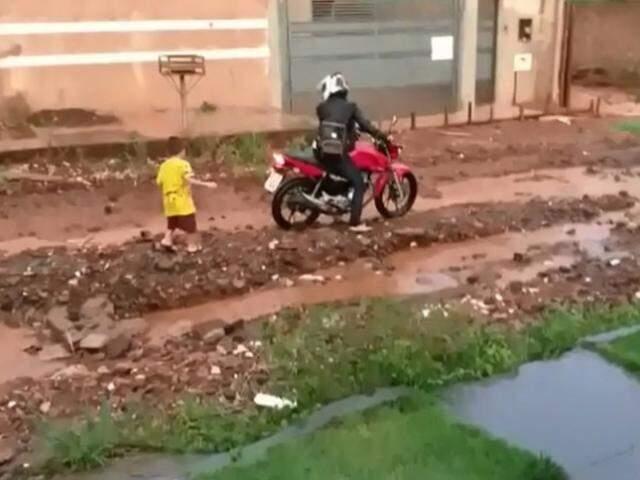 Motociclista com dificuldade para passar por trecho esburacado de rua no Oliveira I (Foto: Direto das Ruas)