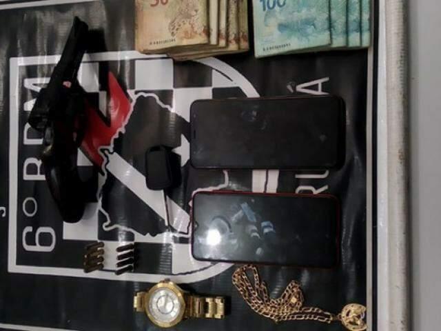 Arma, jóias e dinheiro apreendido no caso. (Foto: Diário Corumbaense)