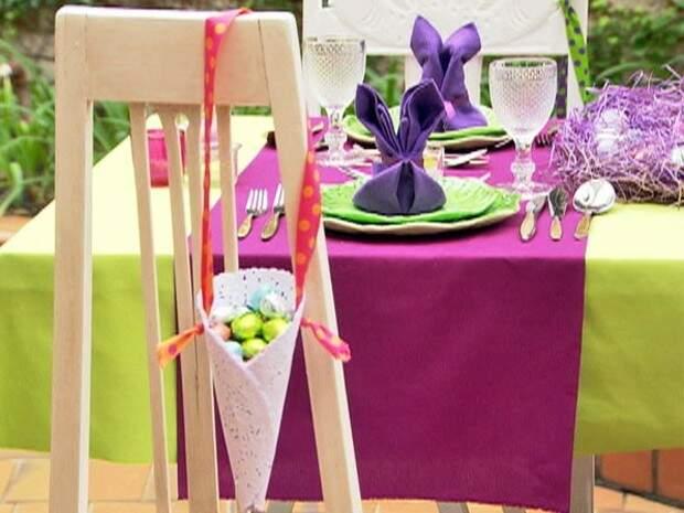 Cone com ovinhos de chocolate e uma mesa super colorida no jardim.