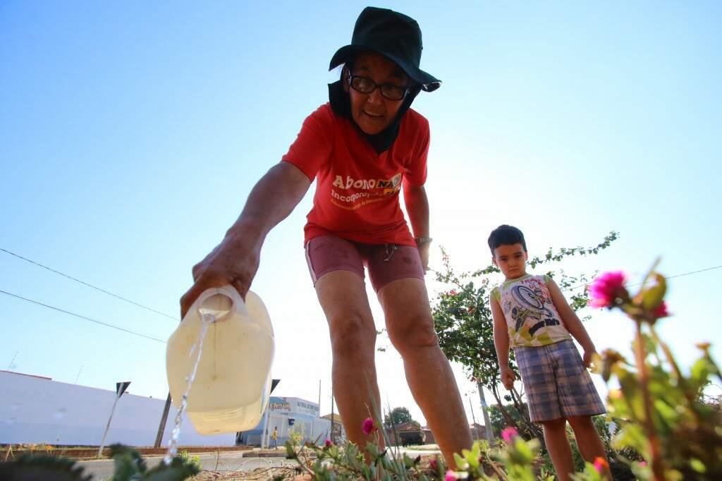 Na companhia do neto, dona Doracy joga água nas plantas todos os dias (Foto: André Bittar)