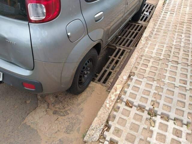 Carro estacionado em cima de boca de lobo com grades quebradas (Foto: Direto das Ruas)