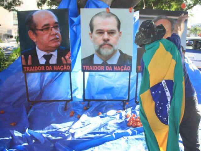 Lona fixada em árvore e fotos de ministros serviram de alvo de artilharia durante ato. (Foto: Marina Pacheco)