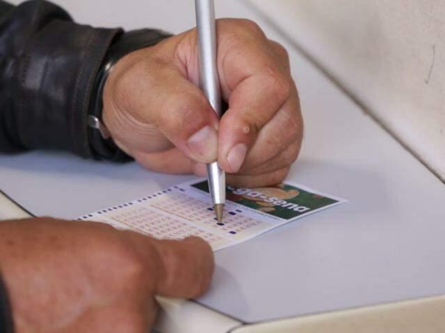Apostador marcando os números da sorte em lotérica da Capital. (Foto: Kisie Ainoã)