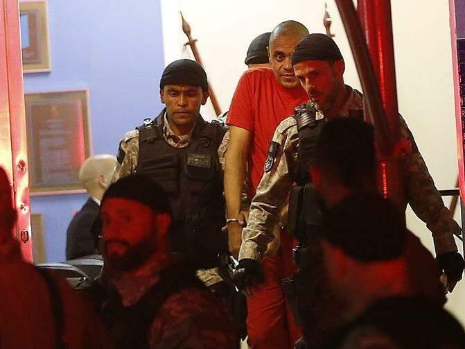 Agressor (de laranja) escoltado por policiais durante transferência. (Tomaz Silva/Agência Brasil/Agência Brasil).