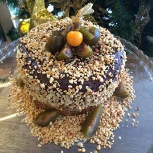 Com castanhas, bolo funcional decorado, com cobertura de chocolate sem glúten e lactose.