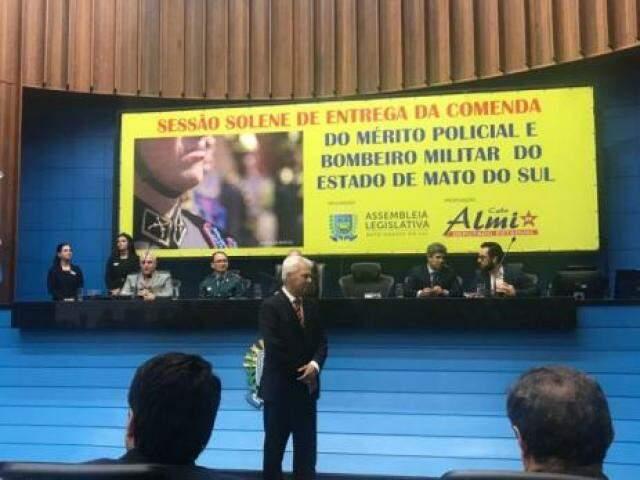 O deputado Cabo Almi (PT), em pé, em frente ao painel com o nome de MS escrito errado. (Foto: Direto das Ruas)