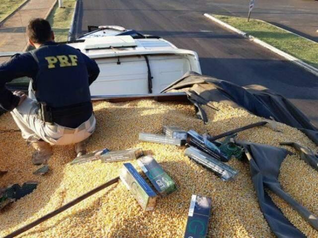 PRF em cima de caminhão carregado com grãos de milho e carteiras de cigarro contrabandeadas (Foto: Divulgação/PRF)