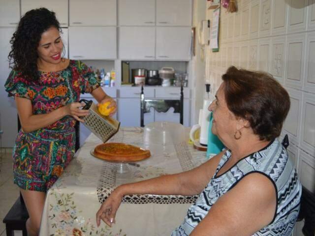 Flávia ralando uma laranja para ser detalhe do bolo da fruta, receita da avó. (Foto: Simão Nogueira)