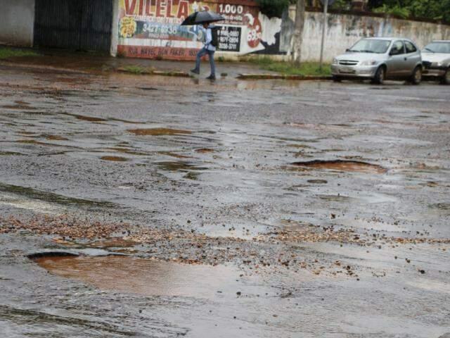 Cruzamento de Dourados tomado por buracos; chuvarada piorou situação e tapa-buraco está parado (Foto: Helio de Freitas)