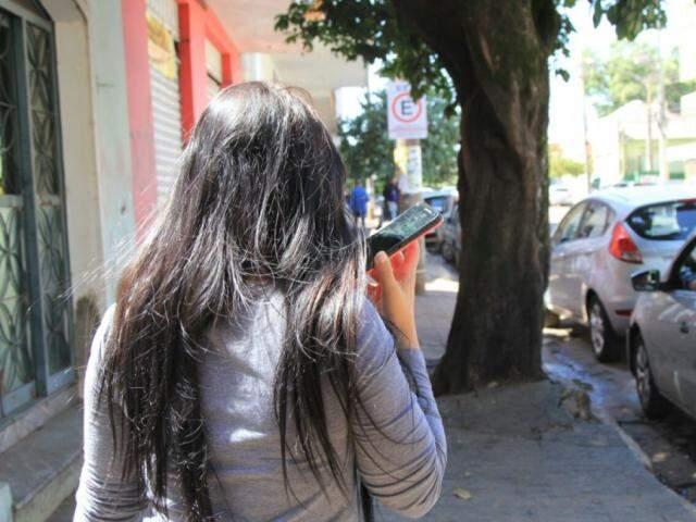 Mulher fala ao celular no Centro de Campo Grande (Foto: Arquivo/Marina Pacheco)