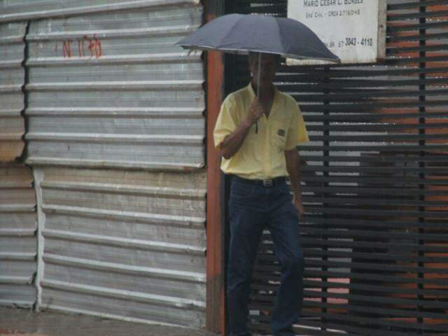 Homem com guarda-chuva em Campo Grande. (Foto: Marcos Ermínio)