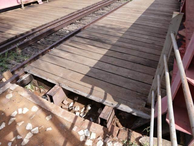 Buraco em deck expõe vigas do pontilhão por onde pedestres passam (Foto: Kisie Aionã)