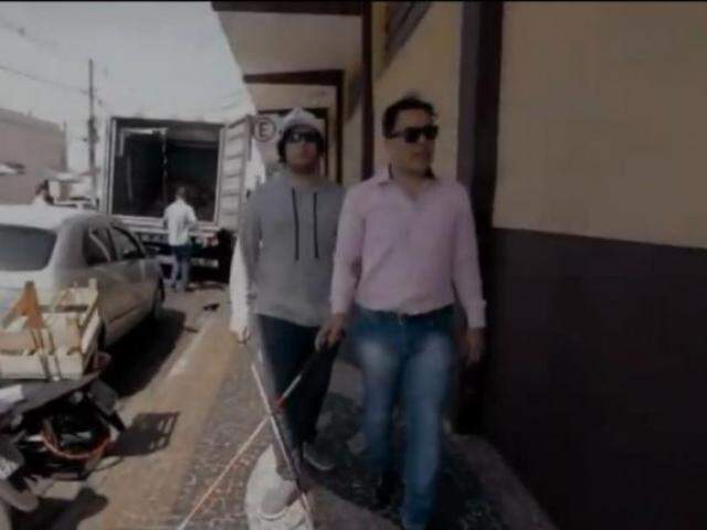 Deputado, de camisa rosa, usa óculos e bengala para simular as dificuldades de quem é cego. (Foto: Reprodução vídeo)