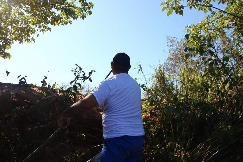 Voluntários se arriscam escalando barrancos para recolher lixo da margem. (Foto: Fernando Antunes)