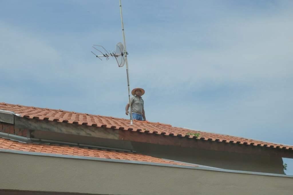 Morador ajuda vizinha recolocando telhas na casa de Sônia.