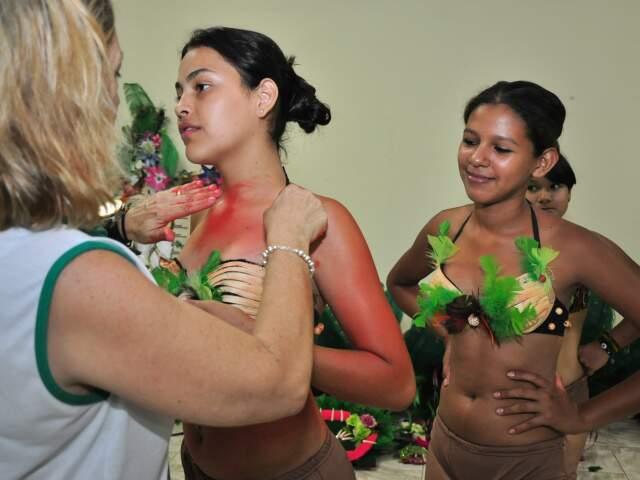Participantes recebem maquiagem e figurino de acordo com cada grupo da apresentação.