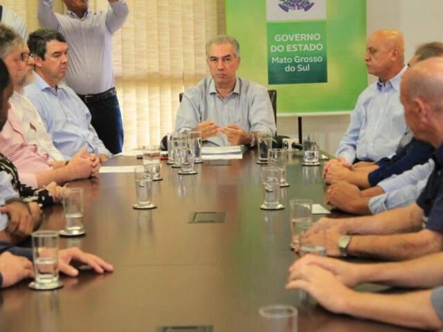 Governador Reinaldo Azambuja (centro) durante anúncio do 13° salário com a participação de secretários e representantes do setor comercial (Foto: Marina Pacheco)