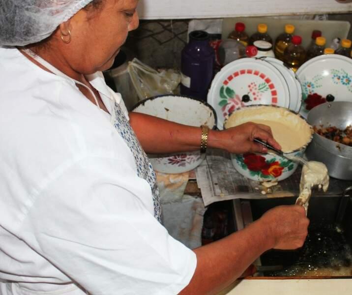 Dona Estácia prepara a massa do Lambreado, na barraca de feira.