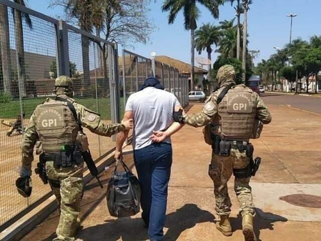 Policiais conduzindo um dos presos na Operação Nepsis, no dia 22 de setembro deste ano (Foto: Adilson Domingos)