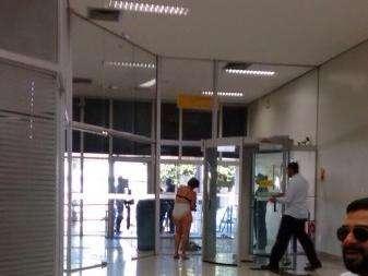 Mulher tira a roupa para passar em porta giratória do Banco do Brasil