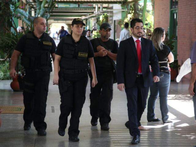 Agentes do Gaeco caminham pelos corredores do Detran durante cumprimento de mandados na última terça-feira (Foto: Marcos Ermínio)