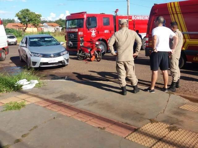 Carro envolvido em acidento ao lado de Biz vermelha e militares dos bombeiros (Foto: Direto das Ruas)