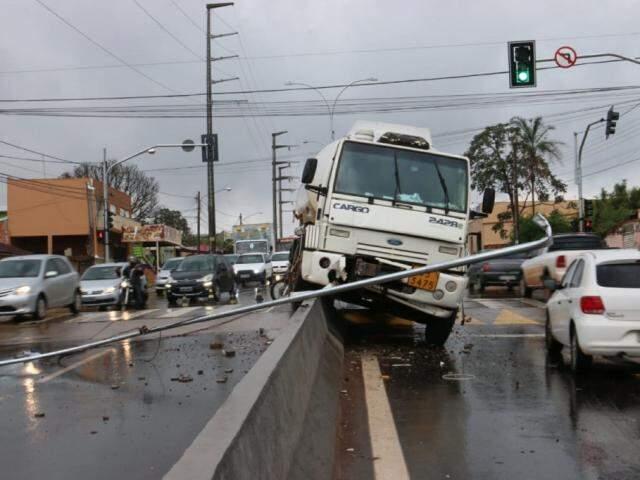 Caminhão em cima de mureta e poste caído na via (Foto: Henrique Kawaminami)