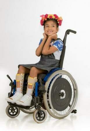 Jardineira infantil foi pensada para vestir a criança sem tirá-la da cadeira de rodas.  (Foto: Antônio Arguello)