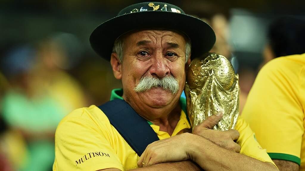 """O """"Gaúcha da Copa"""", Clóvis Acosta Fernandes, chorando abraçado à taça Fifa, na derrota de 7 a 1 do Brasil diante da Alemanha na Copa de 2014 (Foto: (Ivan Pacheco/VEJA)"""