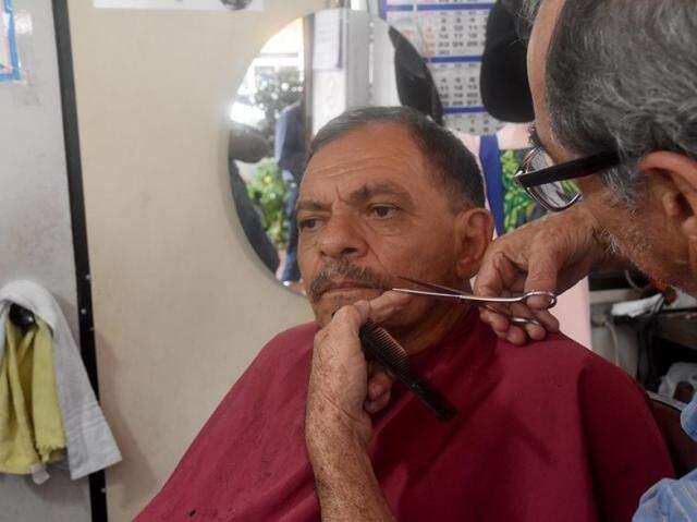 À moda antiga, Toninho só finaliza o corte após aparar o bigode e a sobrancelha de seus clientes. (Foto: Roberto Higa)