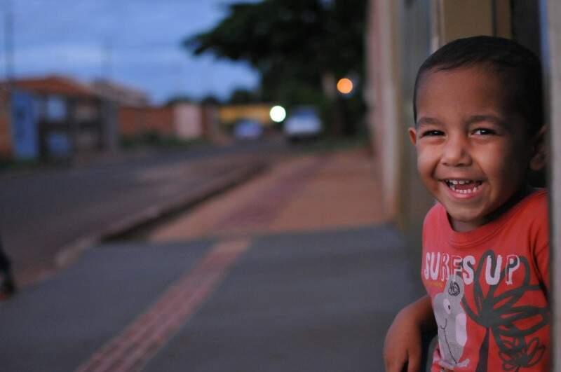O pequeno ajuda a embalar o lixo que eles vem tirar na porta de casa. (Foto: Alcides Neto)