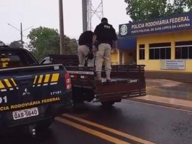Policiais retirando a droga do assoalho do veículo. (Foto: Divulgação/PRF)