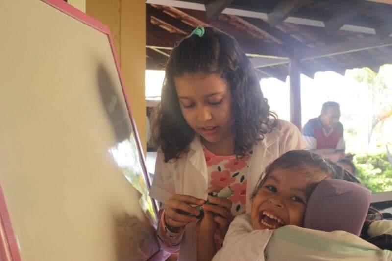 Stela com a pequena Sara, de 5 anos, em frente à lousa. Olha a alegria da menina. (Foto: André Bittar)