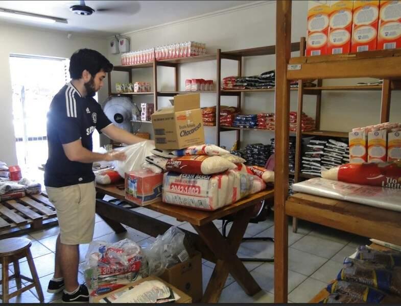 Diogo trabalho no estoque, como voluntário da AACC/MS. (Foto: Laryssa Caetano)