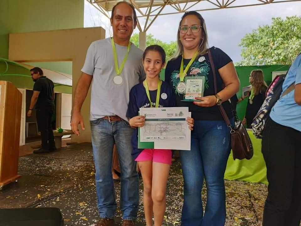 Aluna ao lado dos professores da escola rural após receber o certificado e a medalha de terceiro lugar na feira de Ciências e Tecnologia do Estado  (Foto: Arquivo/E.M.Agrícola Gov. Arnaldo Estevão de Figueiredo)