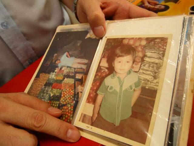 Ele mostra uma de suas fotos, ainda criança, na frente da banca da mãe. (Foto: André Bittar)