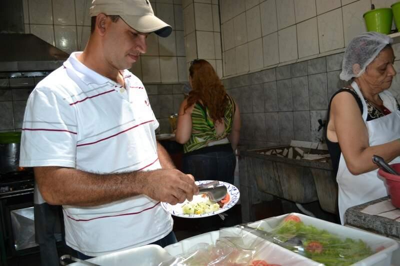 Na cozinha, cliente serve a comida direto das vasilhas e panelas.