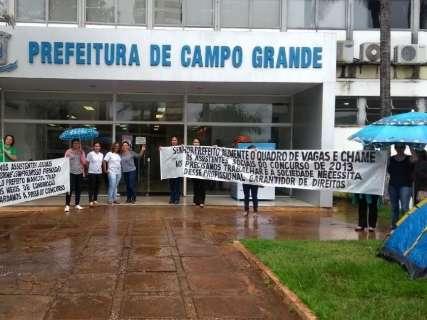 Debaixo de chuva, concursados de 2013 fazem protesto na frente da prefeitura