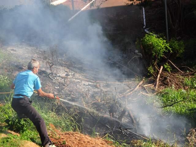Senhor apaga fogo em barranco próximo ao viaduto da Ceará. (Foto: Rodrigo Pazinato)