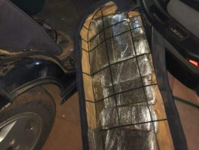 Tabletes de maconha encontrados sob o forro lateral do veículo. (Foto: Divulgação)