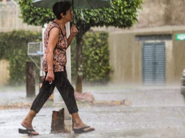 Chuva não pegou essa pedestre desprevenida, que abriu o guarda chuva e continuou a caminhar tranquilamente no Jardim dos Estados (Foto: Marcos Maluf)