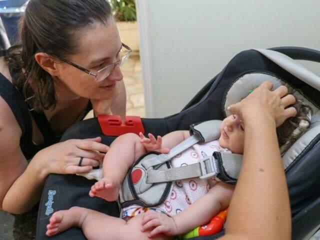 A pequenina Noemi com a mão da terapeuta Patrícia Iasuda colocando as sementinhas sob o olhar atento e carinhoso da mãe Sonia. (Foto: Paulo Francis)