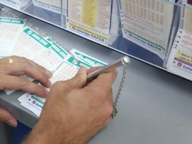 Apostador marcando os números da sorte em lotérica da Capital. (Foto: Paulo Francis)