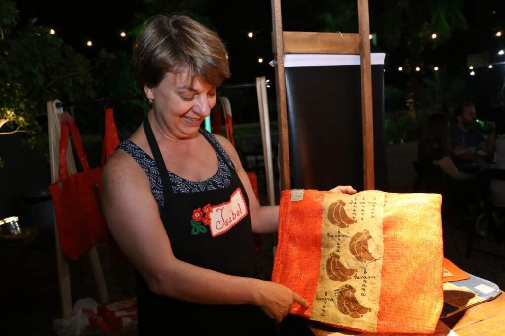 Ela mostra bolsa que confeccionou e usou lona de caminhão para decorar. (Foto: Paulo Francis)