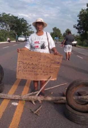 Pescadora segura cartaz com pedido de mudanças (Foto: Direto das Ruas)