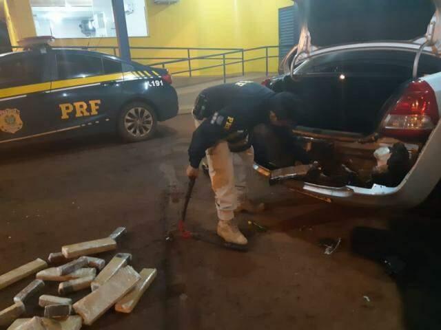 Policial retirando os tabletes da droga da parte traseira do carro. (Foto: Rio Brilhante em Tempo Real)