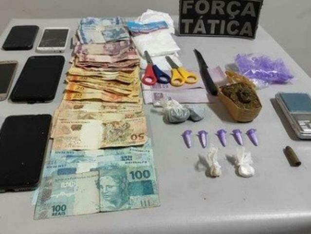 Dinheiro, celulares e drogas apreendidos com os suspeitos. (Foto: Nova Notícias)