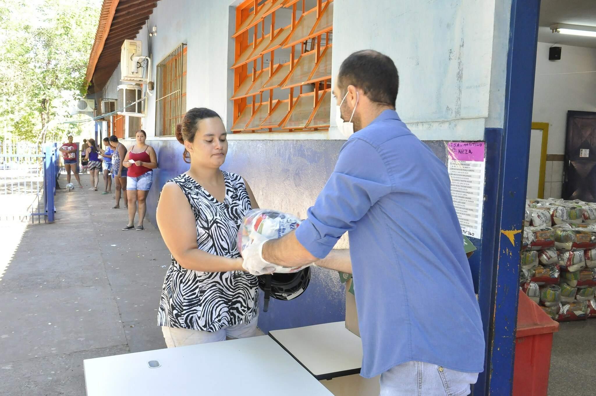 Mãe de aluno recebe kit para alimentar filho enquanto escola estiver fechada (Foto: PMCG/Divulgação)